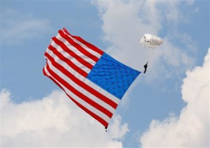 A parachutist dives with the American flag during the National Anthem before the STP NASCAR Nationwide Series race at Chicagoland Speedway on July 21, 2013 in Joliet, Illinois. (Credit: Jonathan Daniel/Getty Images)