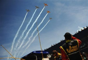 Clint Bowyer, driver of the #15 5-hour ENERGY Toyota, waches as five T-34's from Hooligan's Flight Team perform a flyover prior to the NASCAR Sprint Cup Series Quicken Loans 400 at Michigan International Speedway on June 15, 2014 in Brooklyn, Michigan.Credit: Will Schneekloth/Getty Images