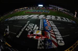 Kevin Harvick, driver of the #4 Budweiser Chevrolet, takes the checkered flag to win the NASCAR Sprint Cup Series Bank of America 500 at Charlotte Motor Speedway on October 11, 2014 in Charlotte, North Carolina.Chris Trotman/NASCAR via Getty Images